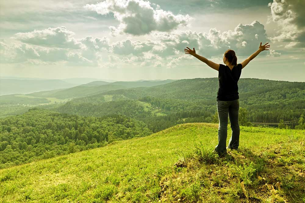 Woman on hill with her arms out toward the sky 'embracing the day'